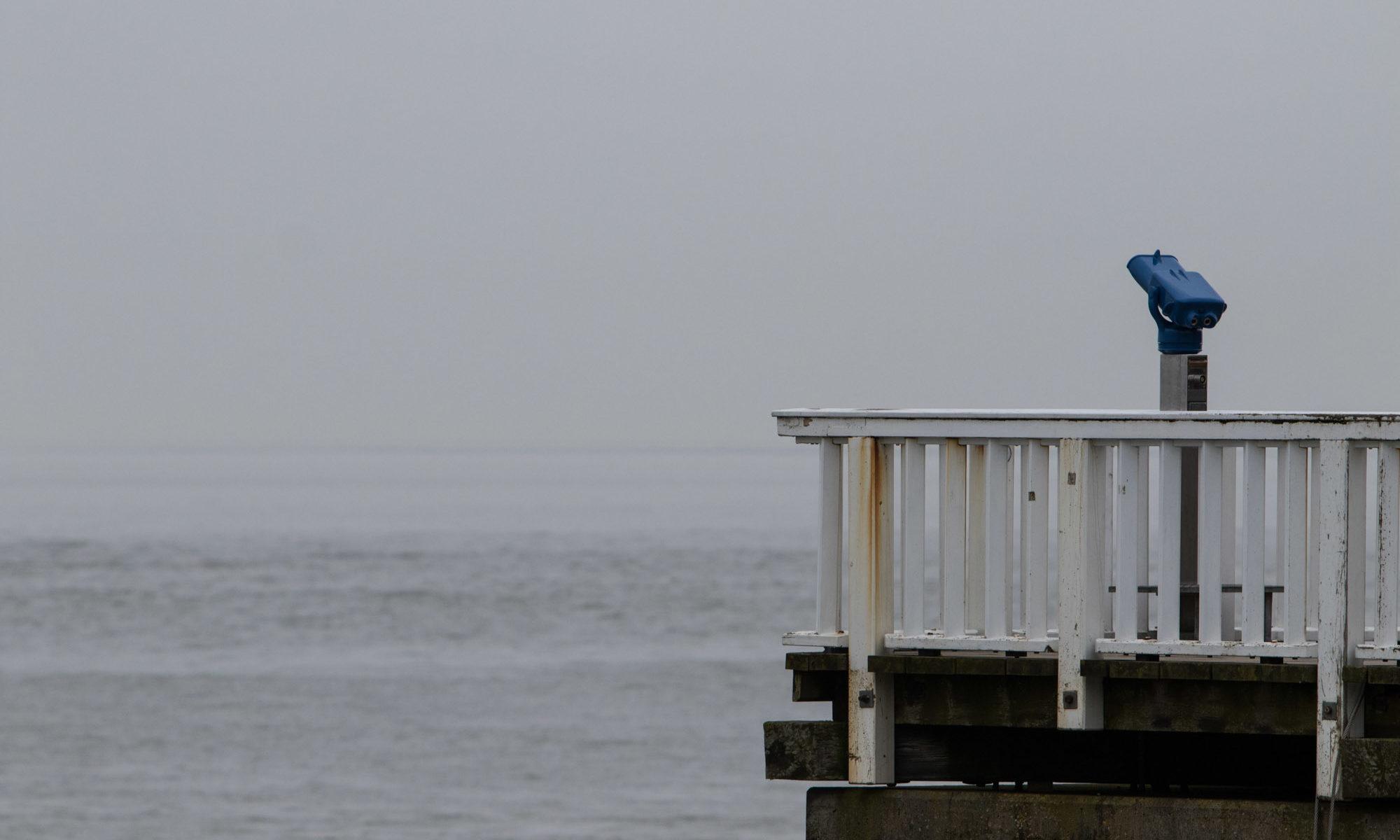 Blaues Fernrohr mit Meer im Hintergrund.