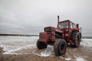 Ein roter Volvo Traktor am Strand im Meerwasser.