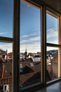 Blick durch ein Fenster über die Dächer von Bergen in Norwegen.
