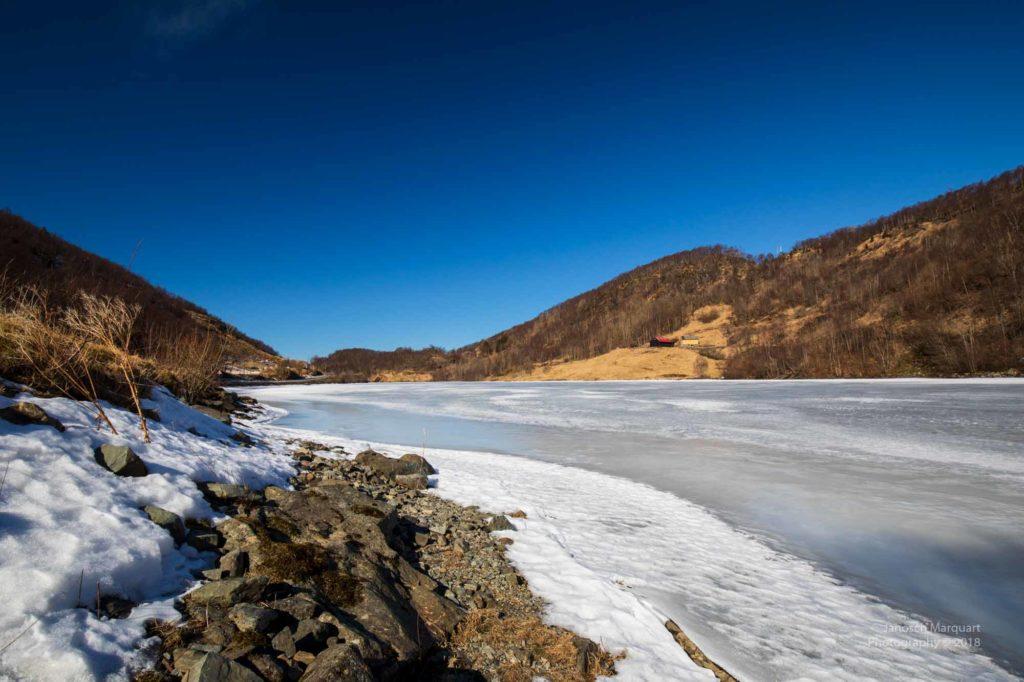 Eine dicke Eisschicht auf dem See auf einer Hochebene
