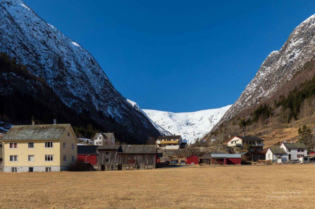 Blick vorbei and Häusern auf den Folgefonna Gletscher.