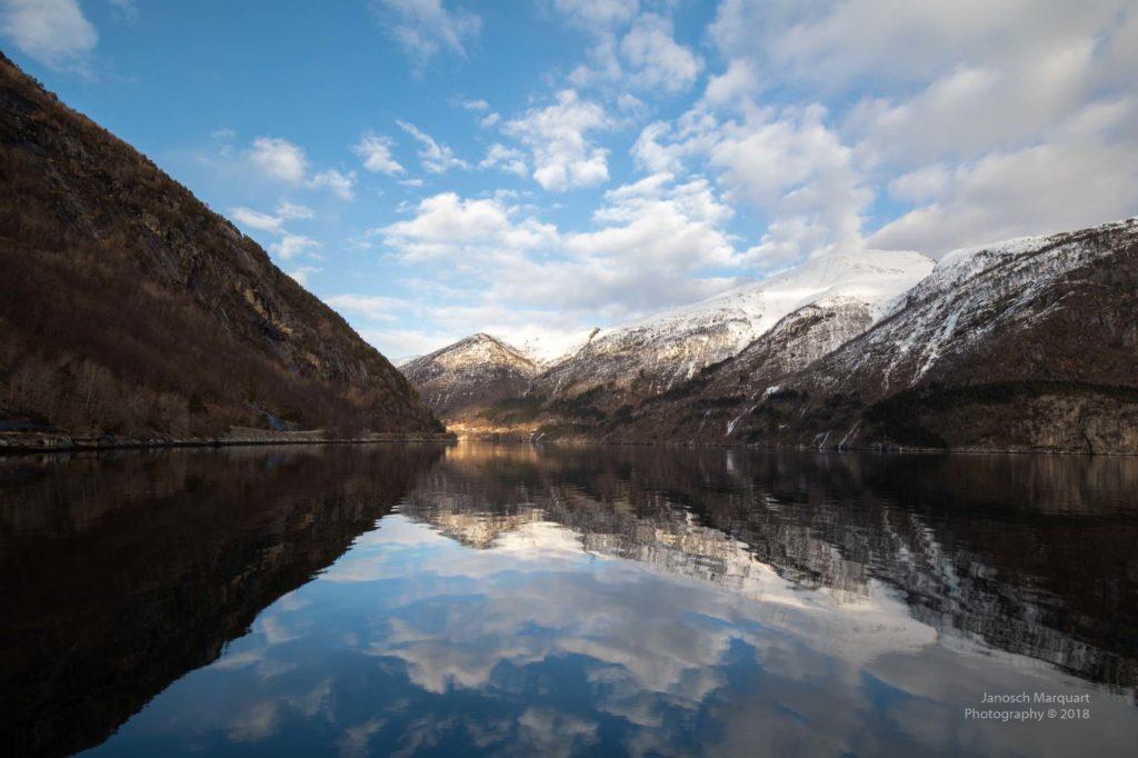 Berghänge am Hardangerfjord mit Wasserspiegelungen.