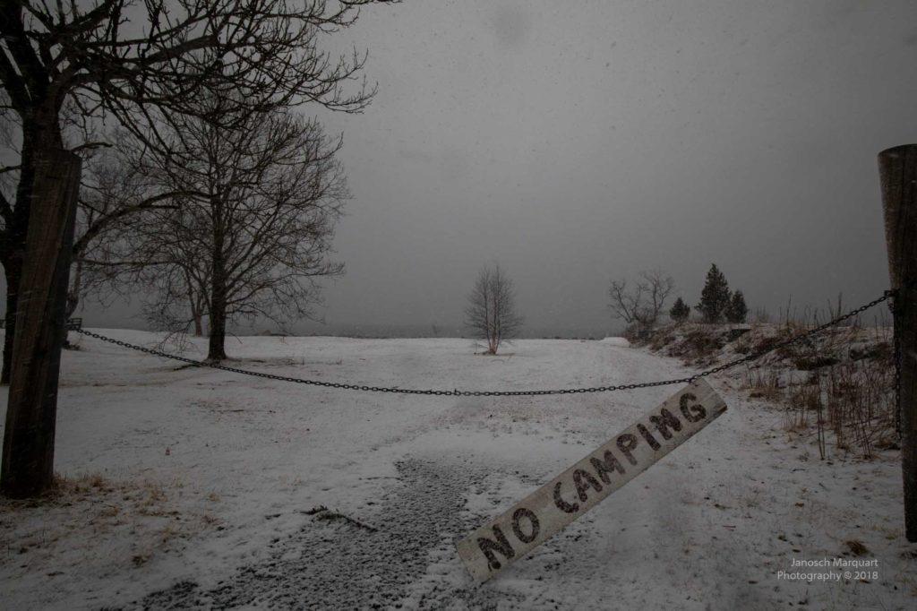 """Weisses, verschneites """"No Camping"""" Schild schräg hängend am Zaun."""