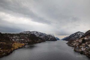 Kleiner Fjord mit verschneiten Bergen.