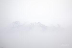 Eine weisse Nebelwand mit ein paar schatierten Bergen.