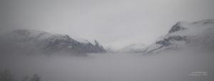 Blick auf die Bergspitzen des Geirangerfjords im Nebel