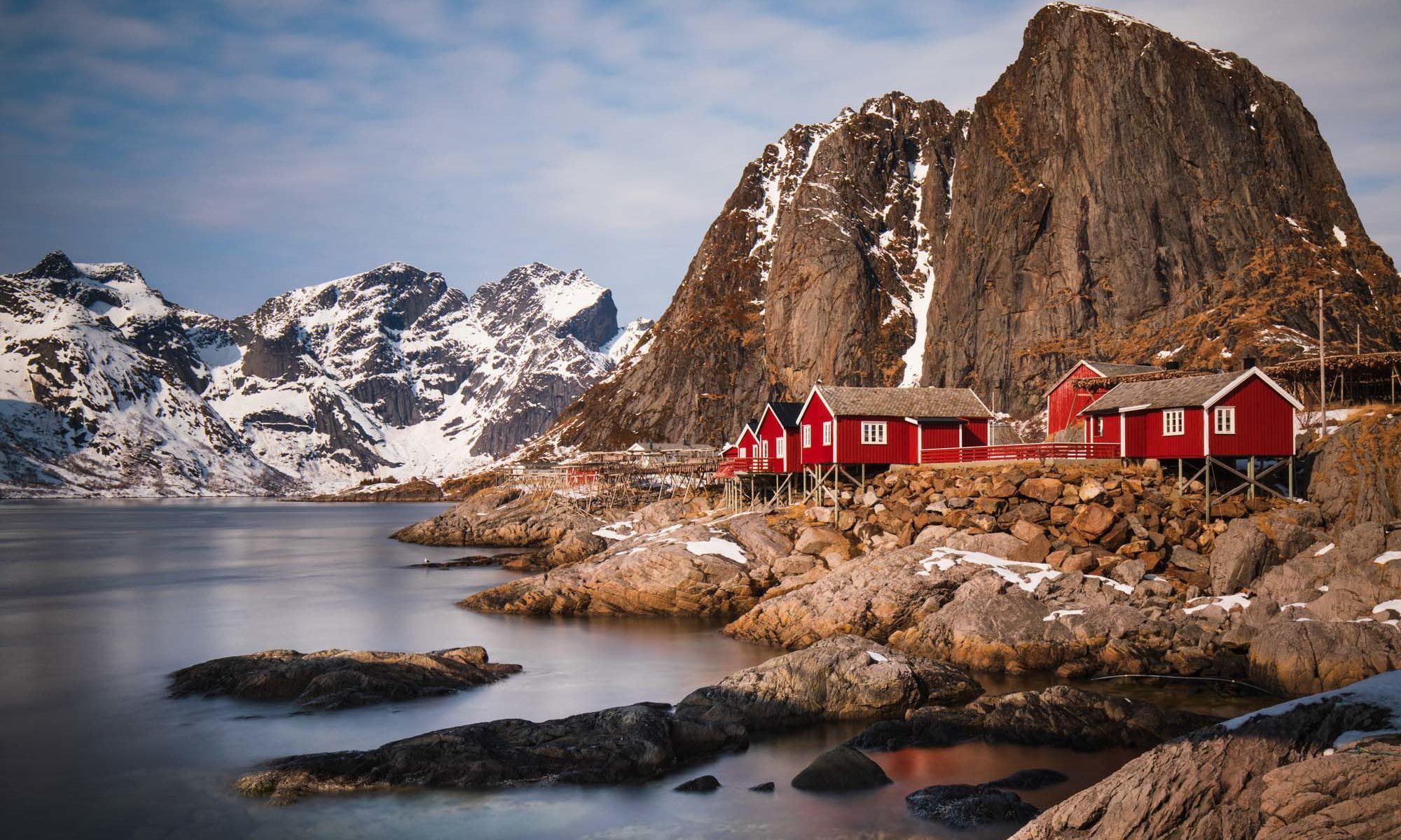 Blick auf rote Rorburer am Meer vor den Bergen auf den Lofoten.