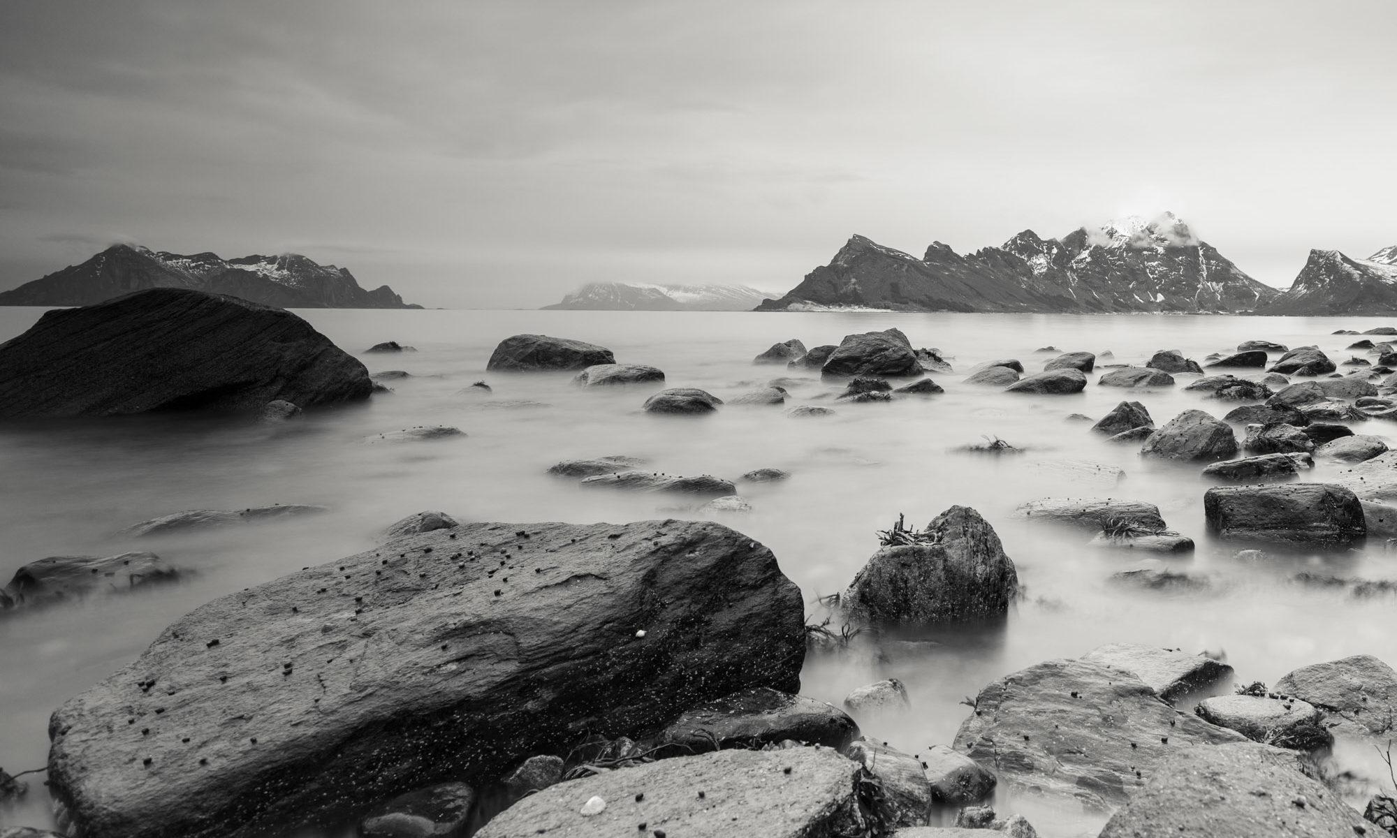 Blick auf vom Wellen umringte Steine vor Bergkulisse