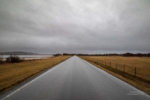 Bild einer regennassen Strasse im flachen Norwegen.