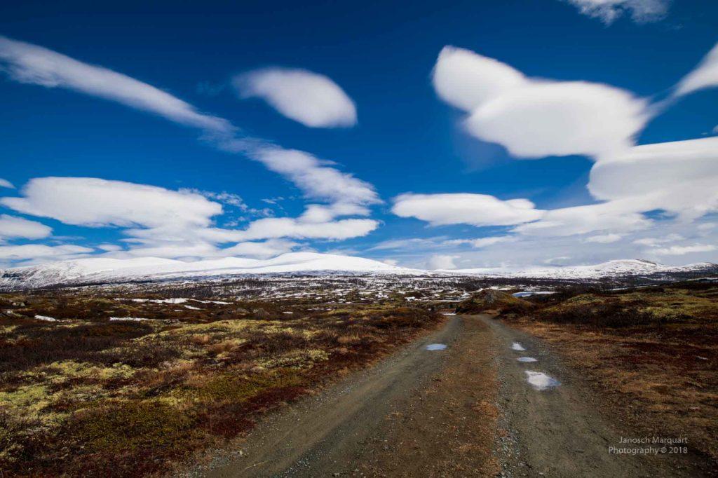 Foto eines Schotterwegs unter blauem Himmel im Dovrefjellnationalpark