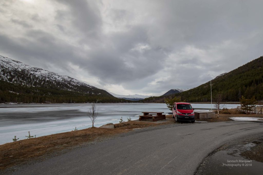 Foto des roten Campervans an einem See.