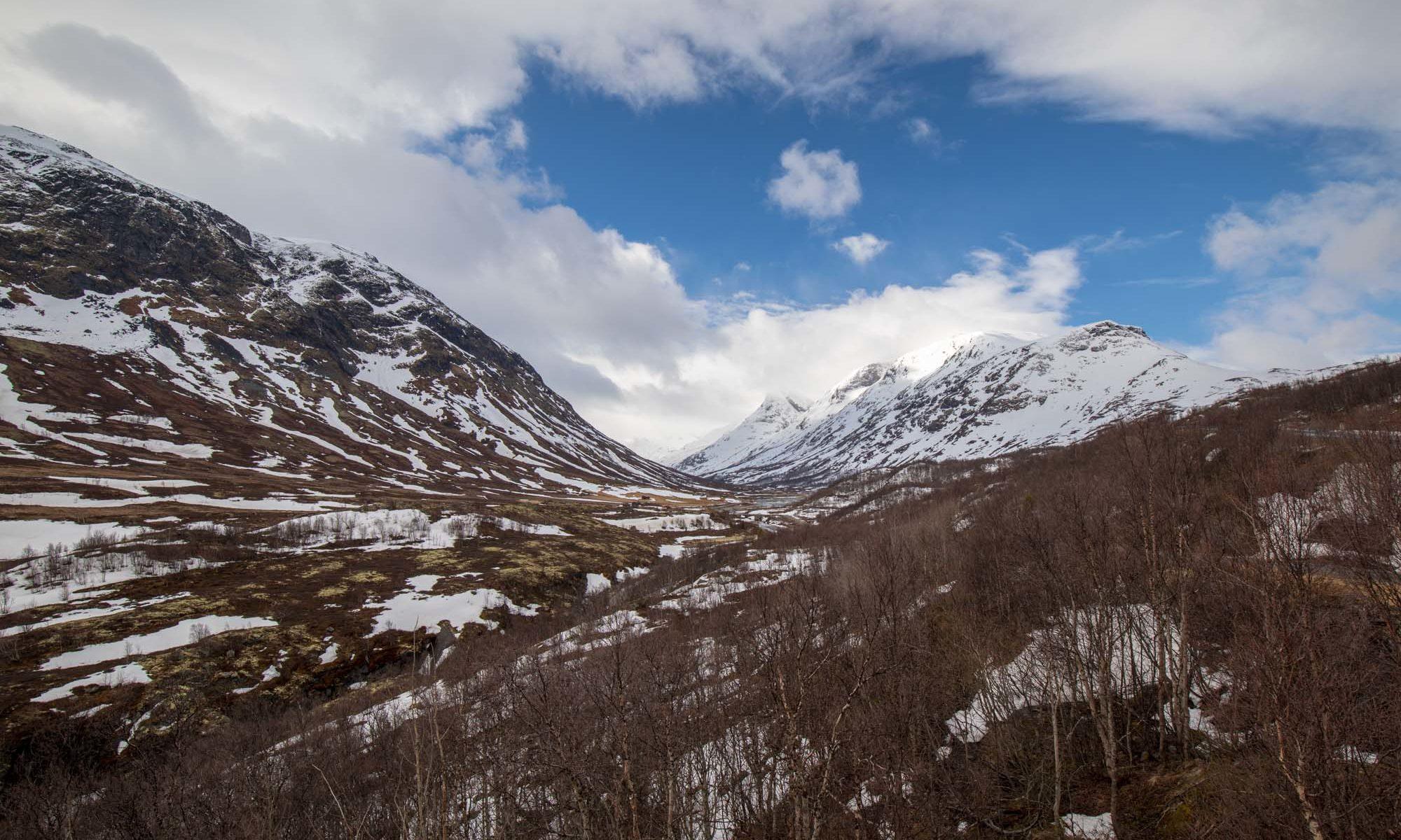 Foto mit Blick auf die Ausläufer des Jotunheimennationalparks im Frühling mit Schnee.