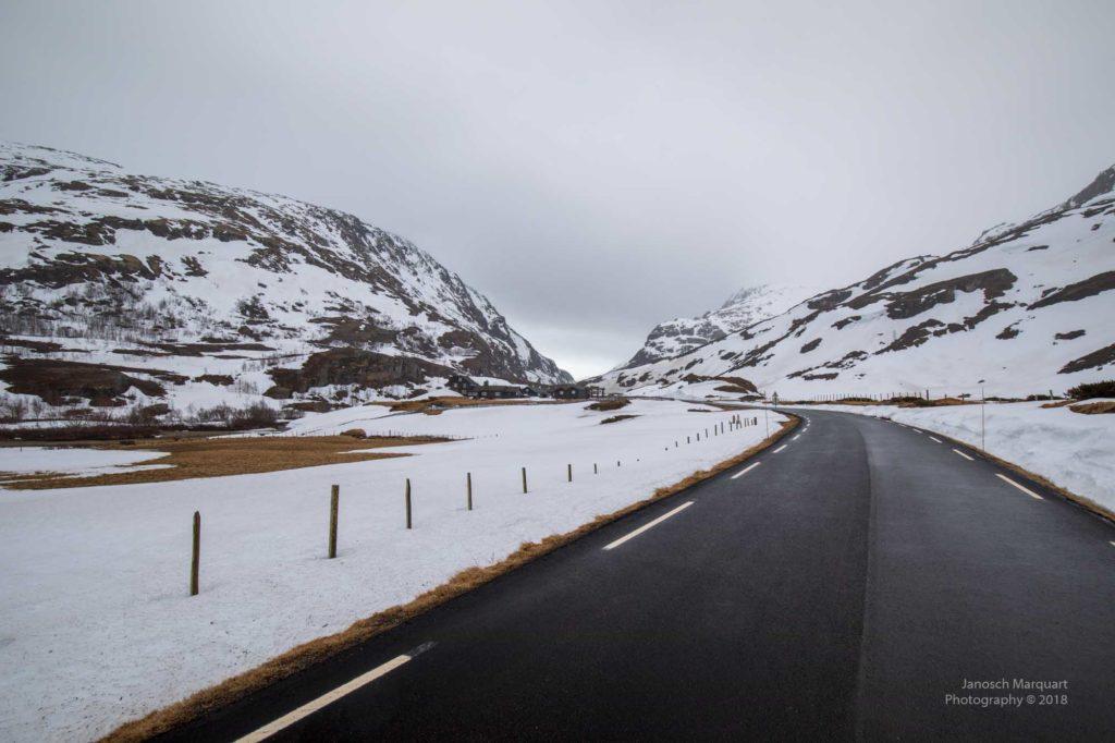 Foto einer Bergstrasse gesäumt von Schnee.