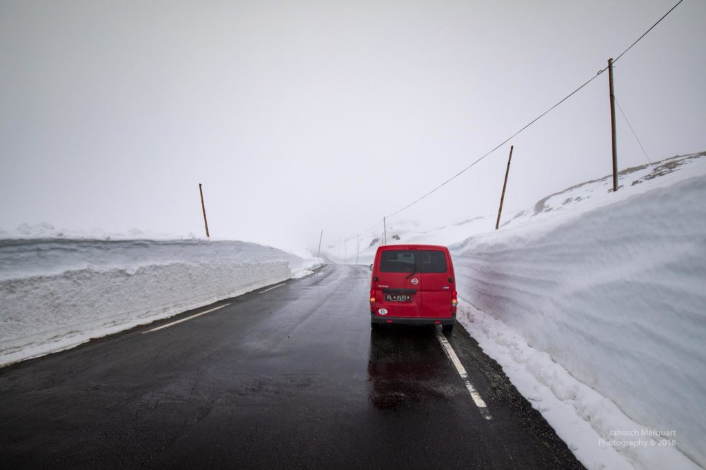 Foto eines Autos eingeramt von Schneewänden neben der Strasse.