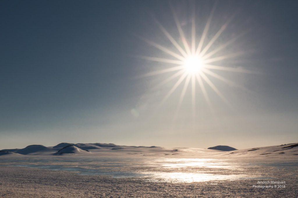 Foto der Sonne über einem verschneiten See auf der Hardangervidda