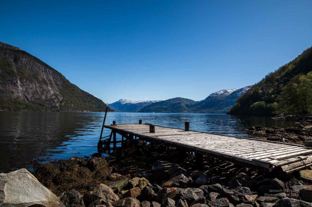 Foto eines hölzernen Bootsanlegers der Solbakken Farm am Hardangerfjord.