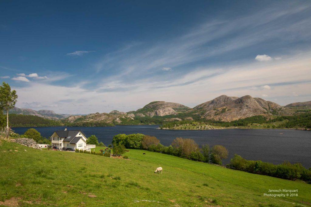Foto eines einsamen Hofs am Fjord.