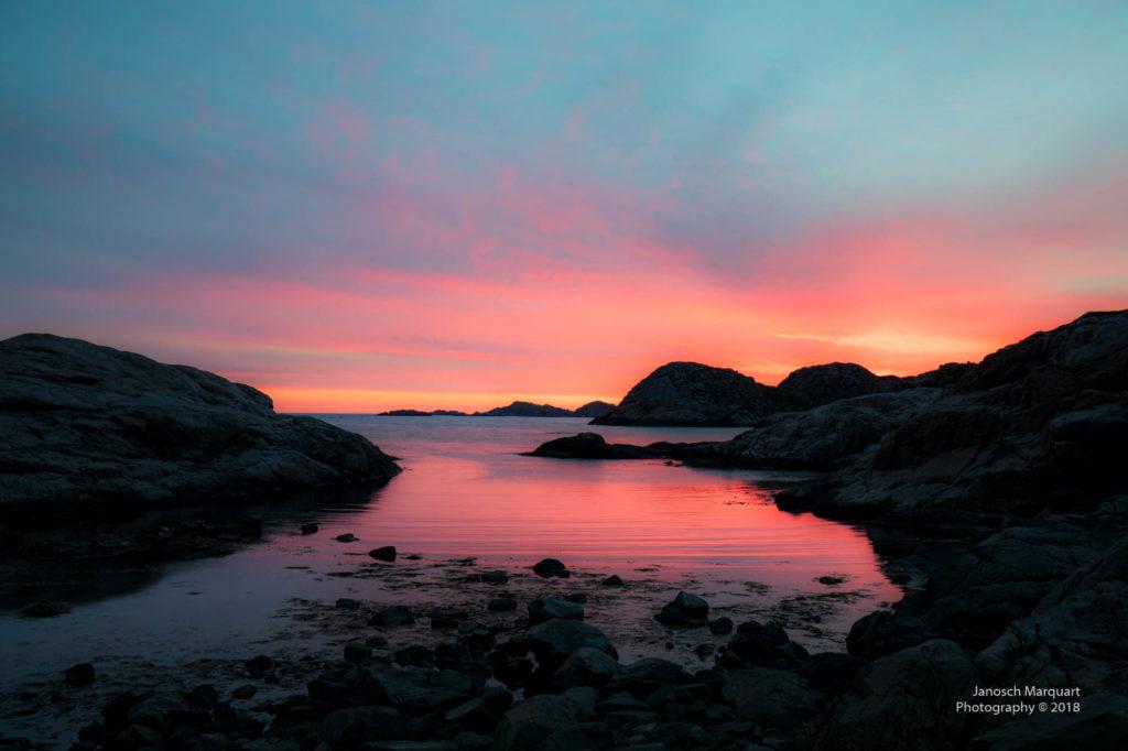 Foto von Wasser und Steinen mit einem rot-gelben Sonnenuntergang am Südkapp in Norwegen.