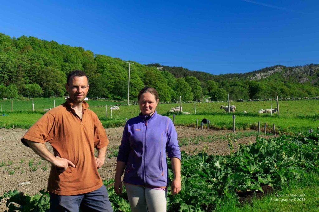 Foto der beiden Hofbesitzer Torill und Jone auf einem Acker.