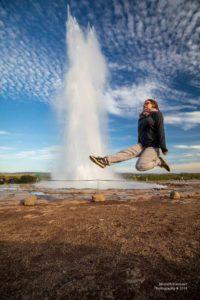 Christina tanzt am Geysir während im Hintergrund heisses Wasser aus dem Boden schiesst.