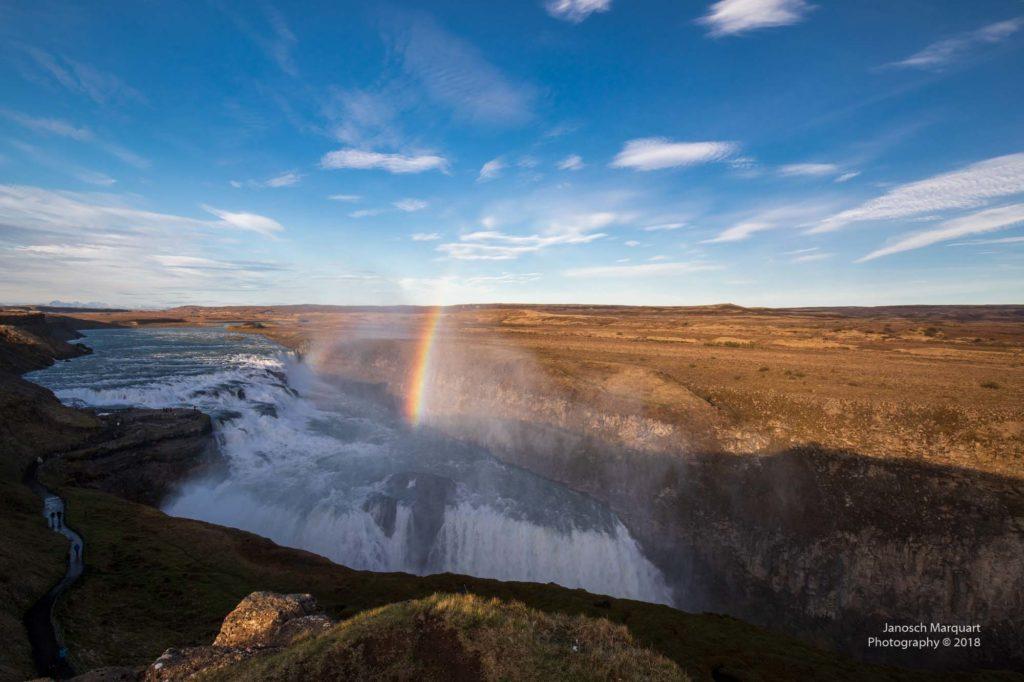Foto des Gullfoss Wasserfalls mit einem Regenbogen.