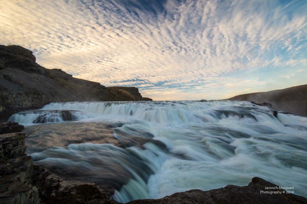 Foto der oberen Stufe des Gullfoss Wasserfalls im Abendlicht mit Wolkenhimmel.