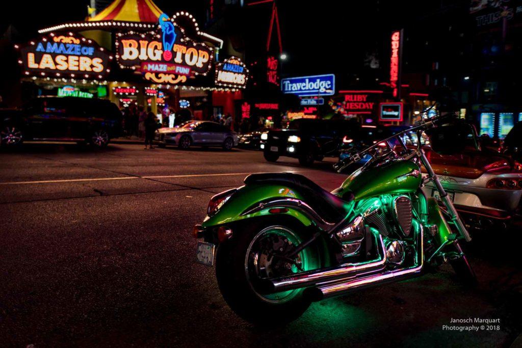 Foto einer grün beleuchtet Harley in Vergnügungsmeile.