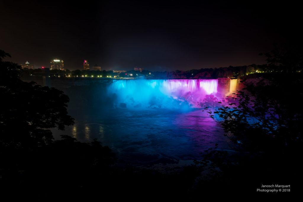 Foto der farbig beleuchteten American Falls als Teil der Niagara Falls.