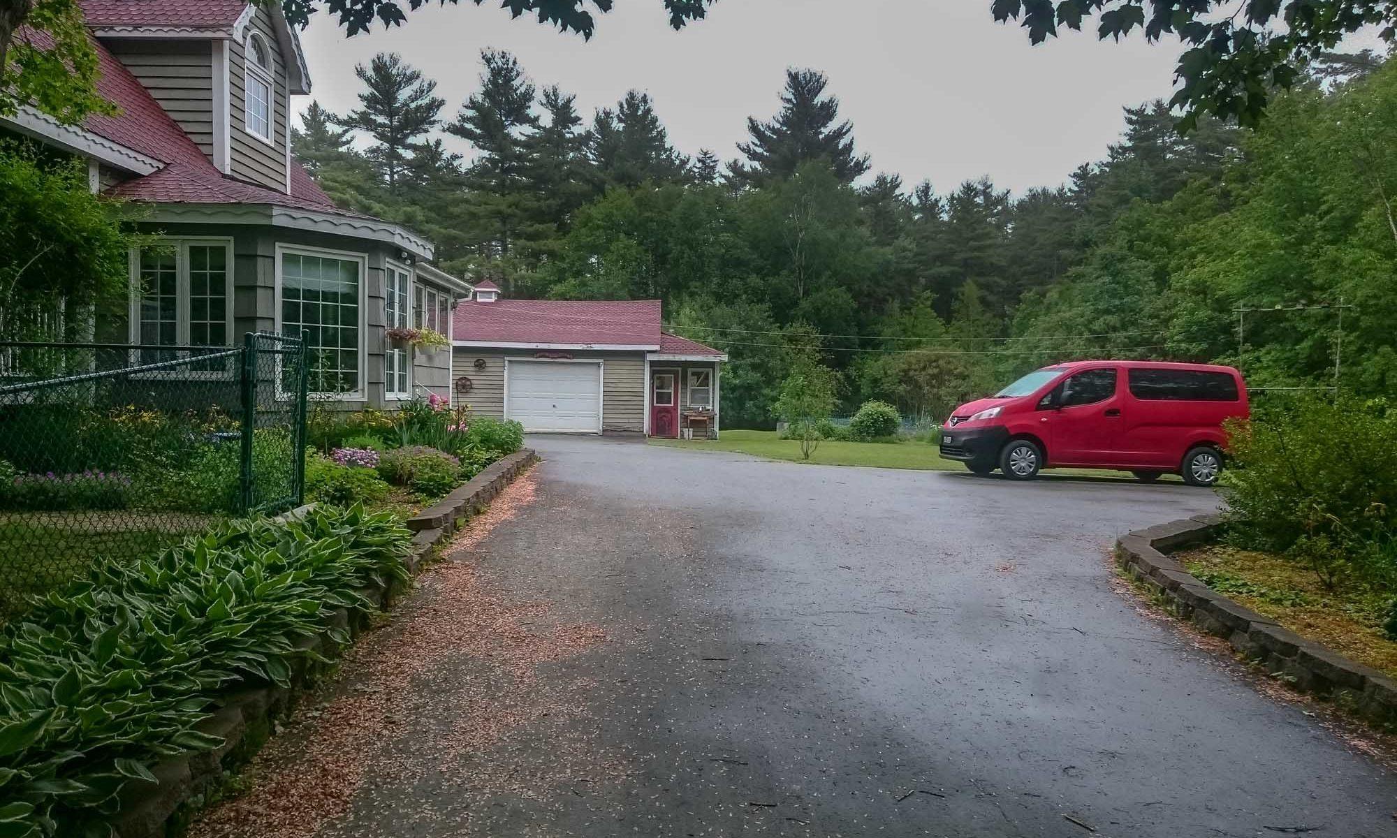 Foto einer Hauszufahrt mit rotem Camper.