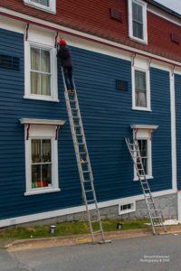 Foto eines Malers auf einer Leiter in Lunenburg.