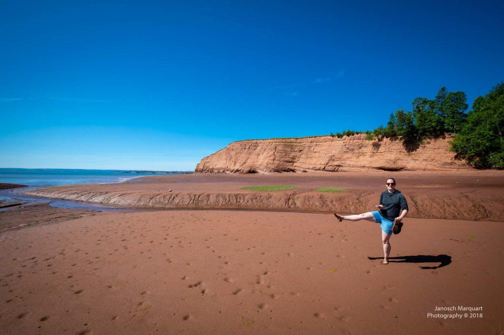 Foto von Christina im roten Schlamm am Strand.