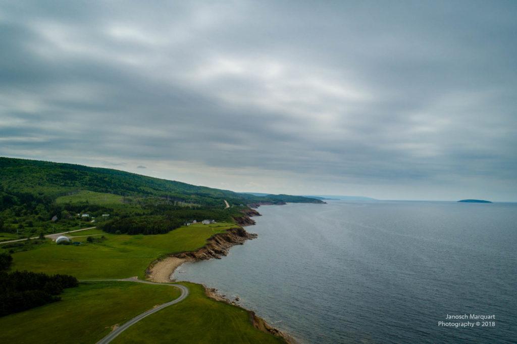 Foto der Küste mit Gras und Sand auf Cape Breton Island.