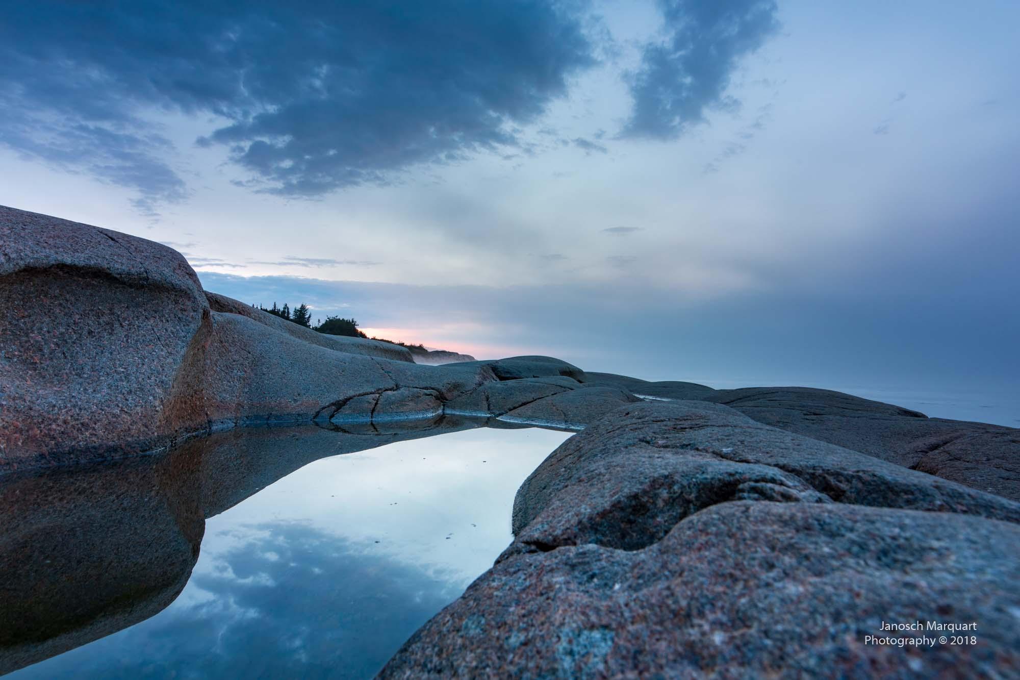 Foto einer Wasserspiegelung zwischen Felsen.