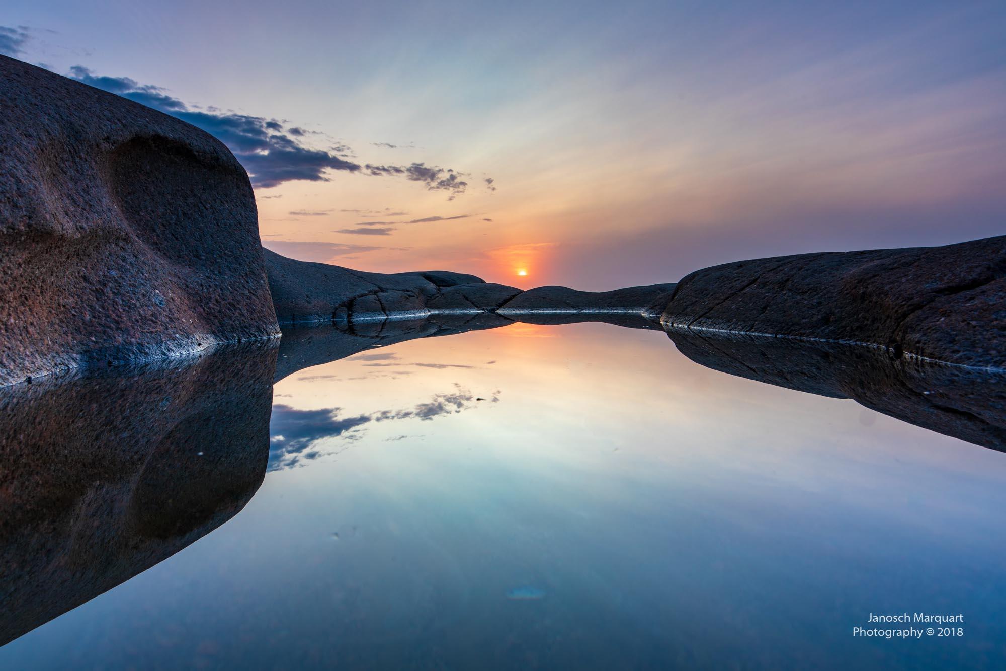 Foto einer Spiegelung des Sonnenaufgangs im Wasser zwischen Steinen.