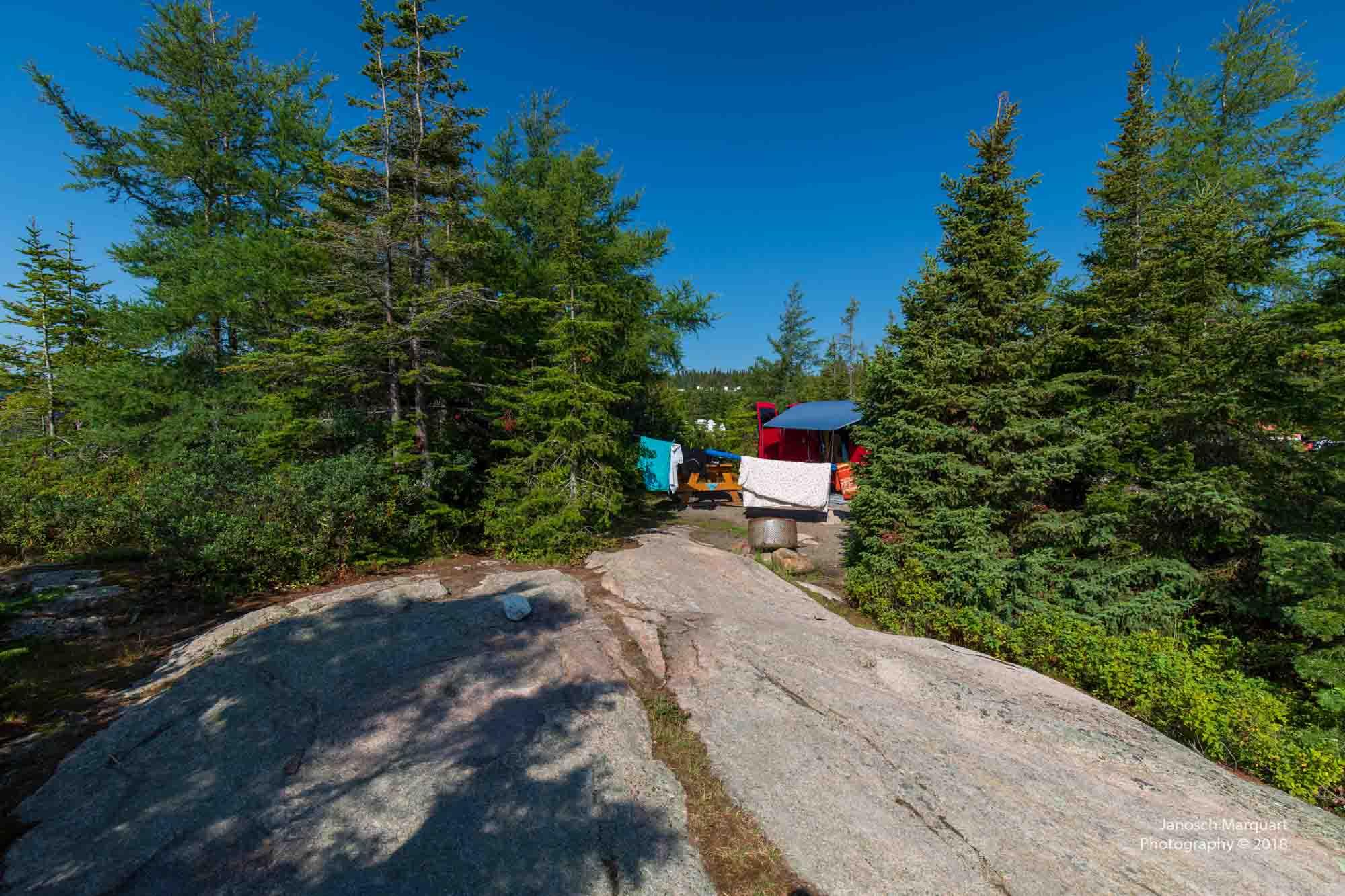 Foto eines privaten Campingplatzes zwischen Bäumen und Felsen.