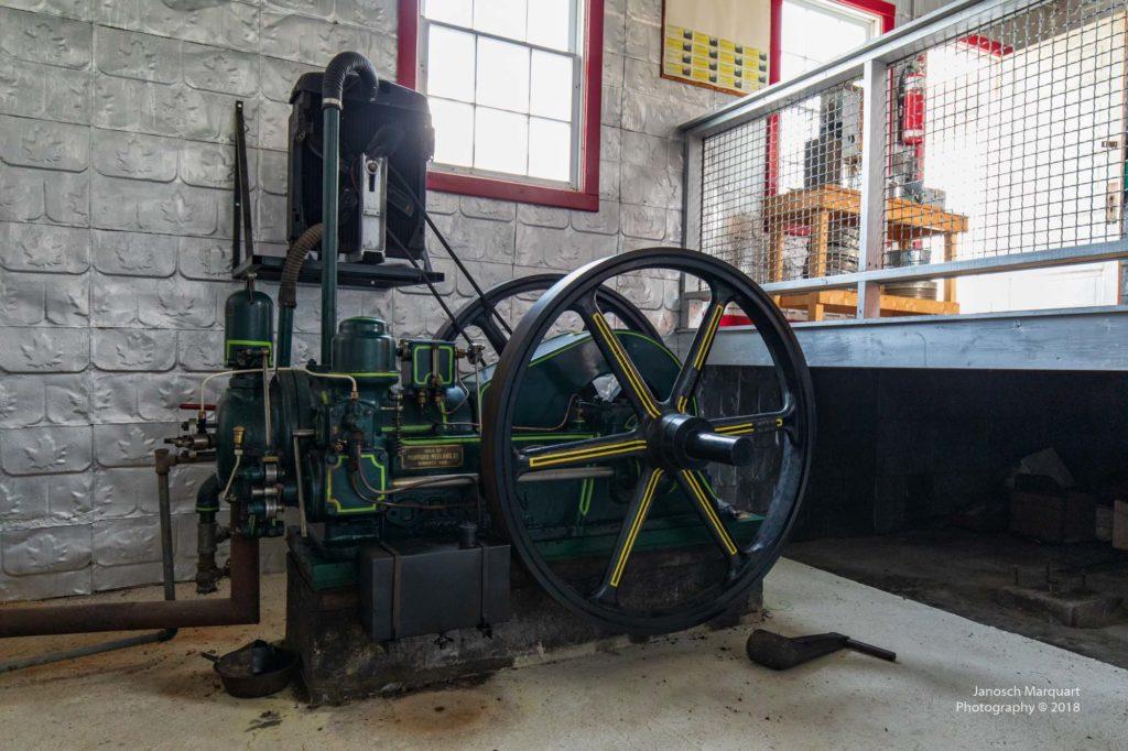 Historischer Dieselmotor in einem abgeschirmten Raum.