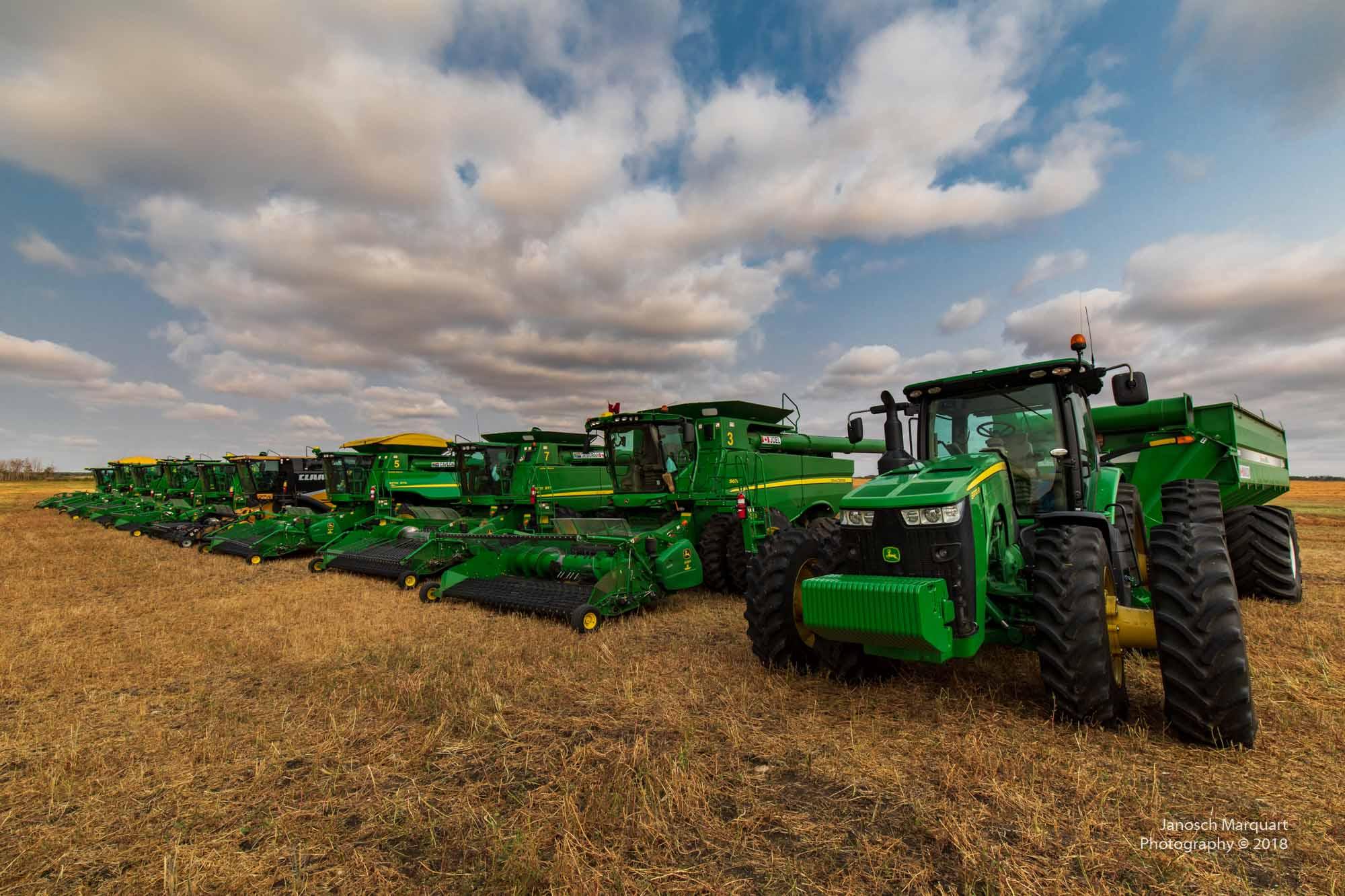 Mehrere Traktoren und Mähdrescher auf Acker.