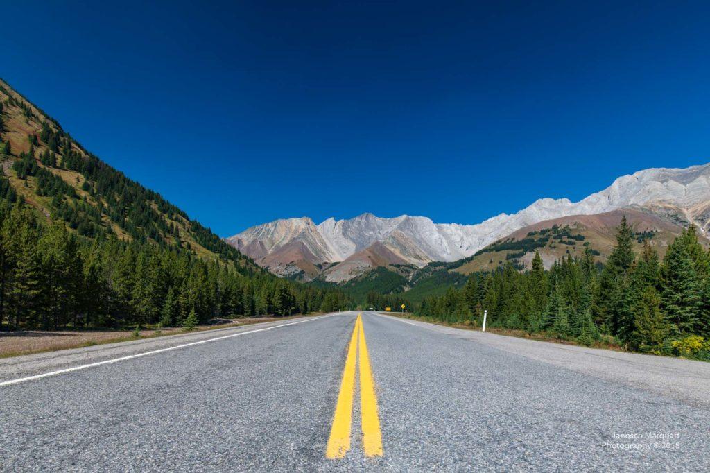 Highway durch die Berge vor blauem Himmel im Kananskis Valley.