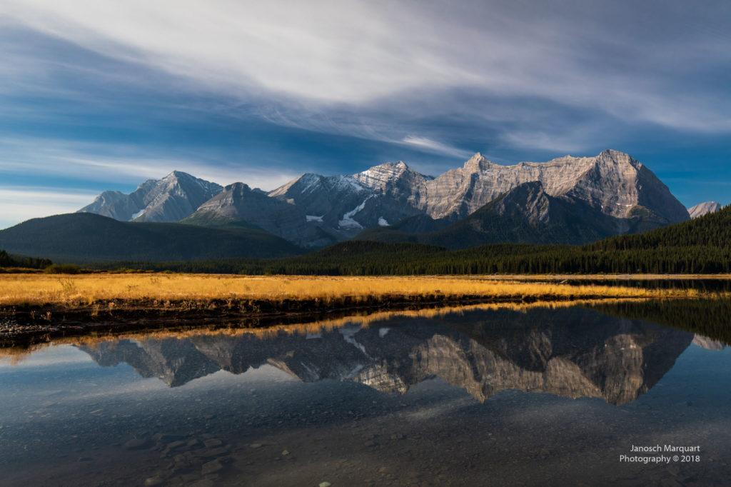 Spiegelung einer Herbstwiese und Berge im Wasser.