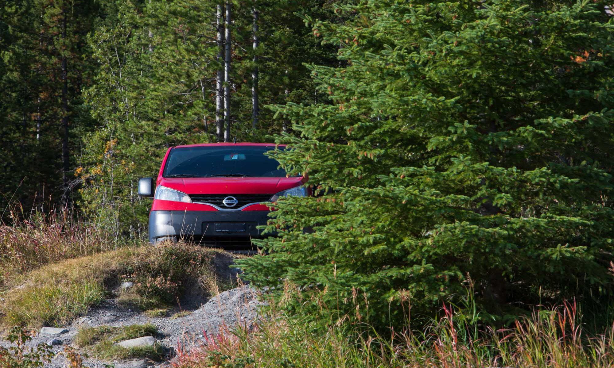 Roter Campervan hinter Bäumen versteckt.