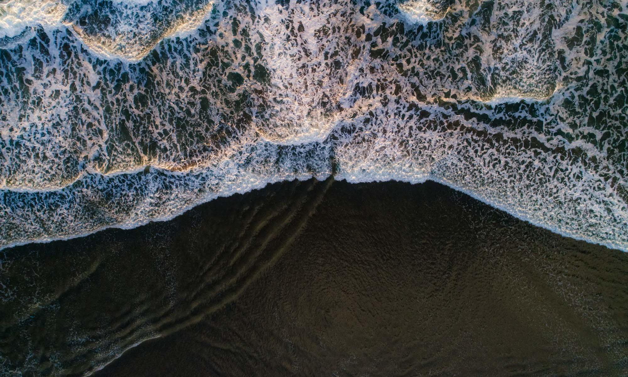 Wellen an schwarzem Strand