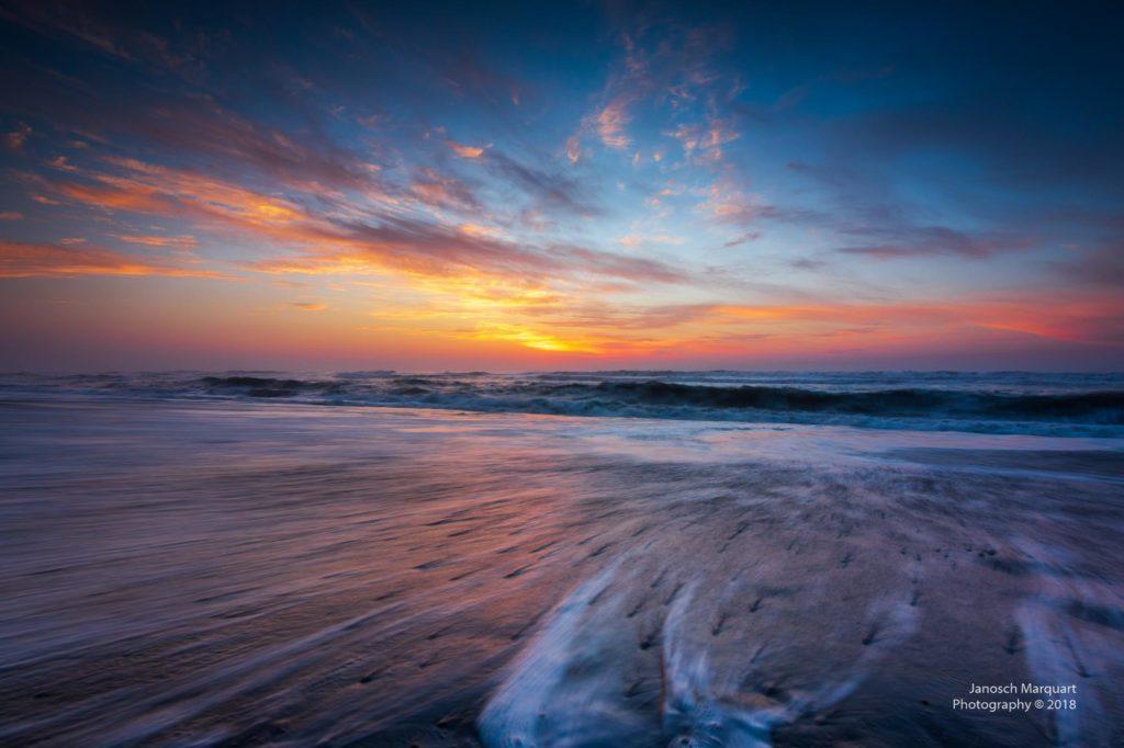 Wellen am Strand bei Sonnenuntergang.