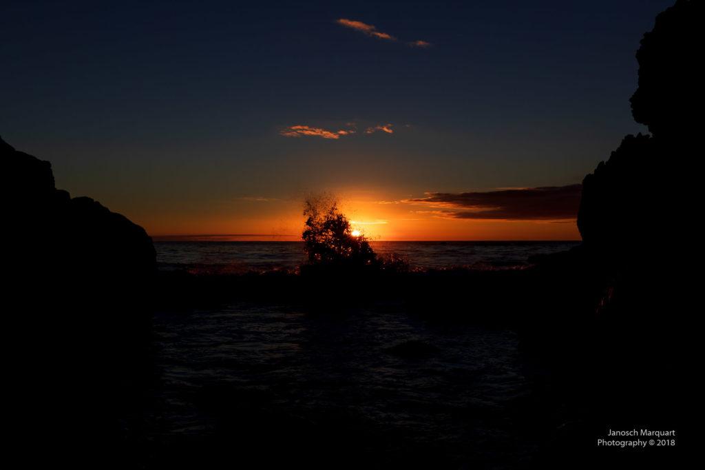 Sonnenuntergang am Meer mit spritzenden Wellen.