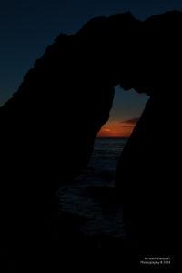 Sonnenuntergang durch Felstor hindurch mit Blick aufs Meer.