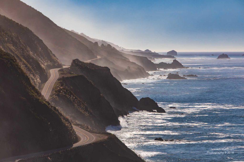 Küstenstrasse im Nebel mit Pazifikbrandung.