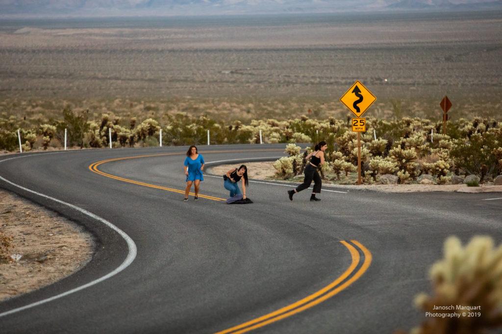 Drei Mädchen beim Fotoshooting auf der Strasse in der Wüste.