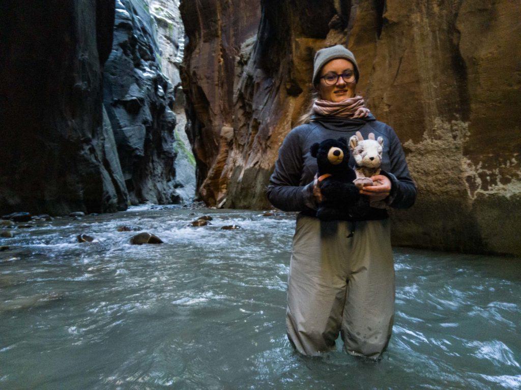 Christina haltet Balznerbock und Beary sicher in den Armen und begleitet sie durch den Fluss.