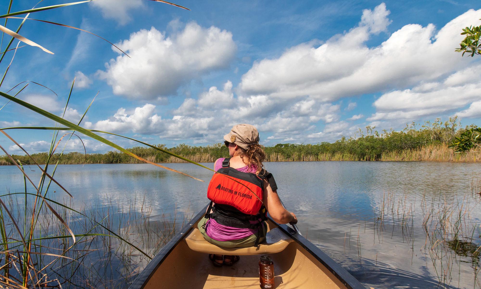 Christina im Kanu zwischen Schilf mit Blick auf See.